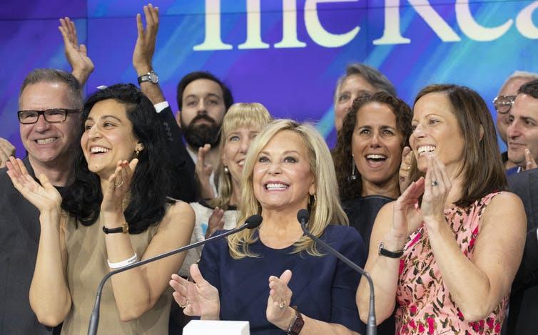 Десять улыбающихся людей в деловой одежде позируют вместе и хлопают в ладоши.